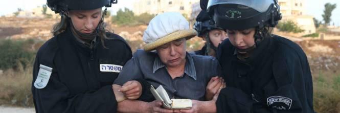 Poliziotte israeliane portano via una anziana colona a Beit El