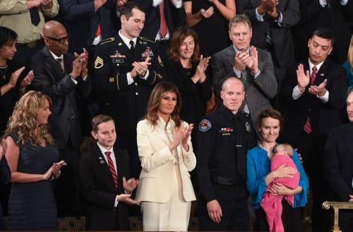 La first lady Melania incanta in bianco. Ma arriva sola e a braccetto di un militare