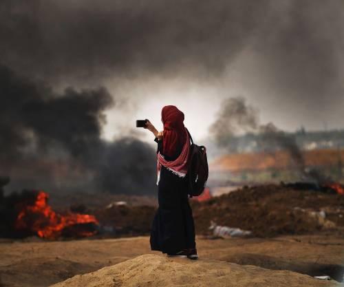 Una donna palestinese registra le violenze al confine con Gaza
