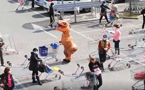 Travestito da dinosauro in coda al supermercato