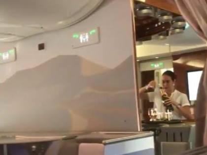 L'hostess del volo Emirates versa lo champagne avanzato in una bottiglia