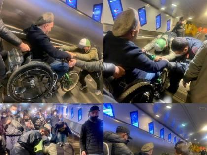 A Roma le scale mobili sono fuori uso e un uomo su sedia a rotelle viene portato in spalla