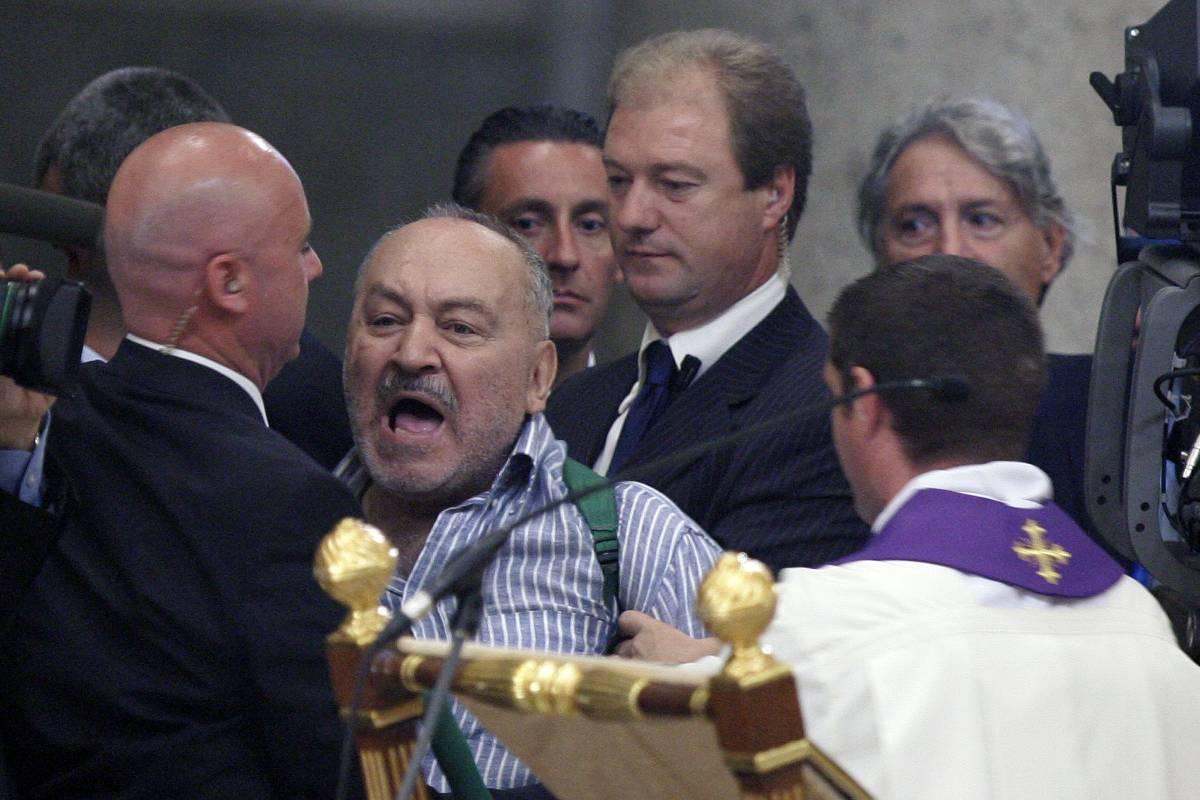 """Un uomo sale sull'altare e grida: """"Pace subito""""  Bossi: """"Ho votato sì, ma non per farli morire"""""""