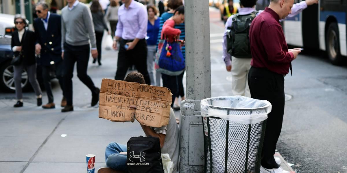 """Un giovane con un cartello che dice: """"Senzatetto 23enne affamato e senza famiglia chiede aiuto e cerca una stanza"""""""