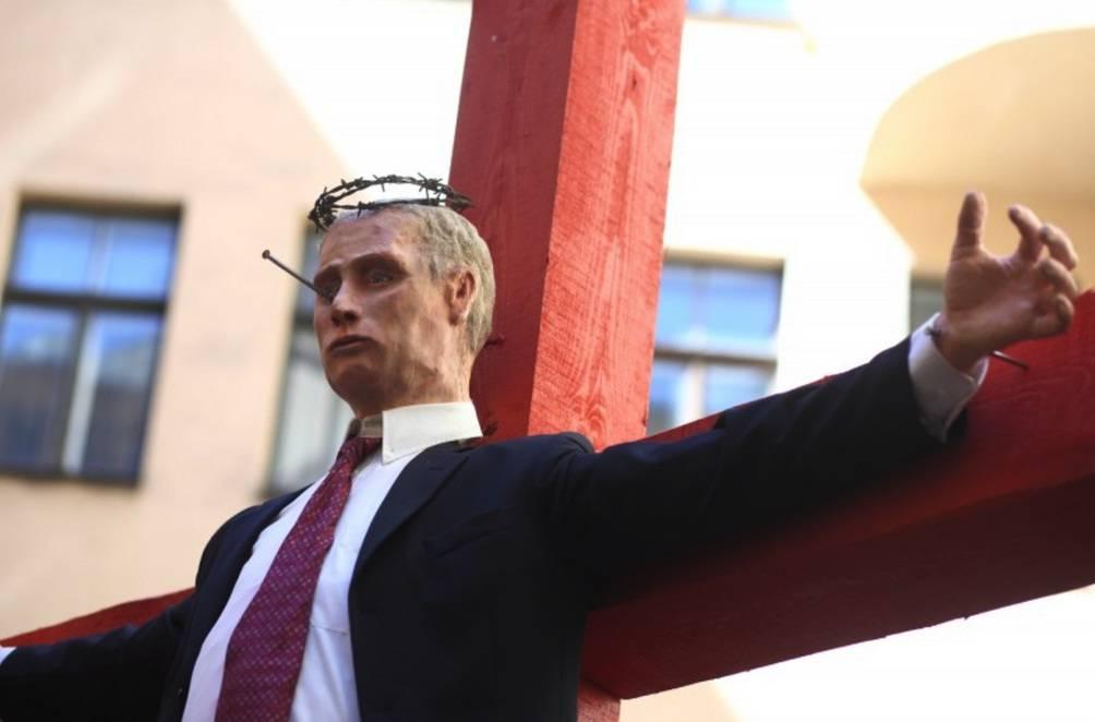 Riga, Putin crocifisso in strada: ogni passante pianta un chiodo