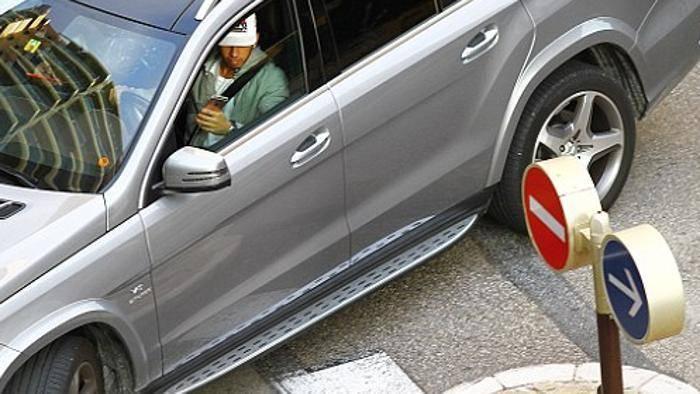 Lewis Hamilton al volante col cellulare in mano