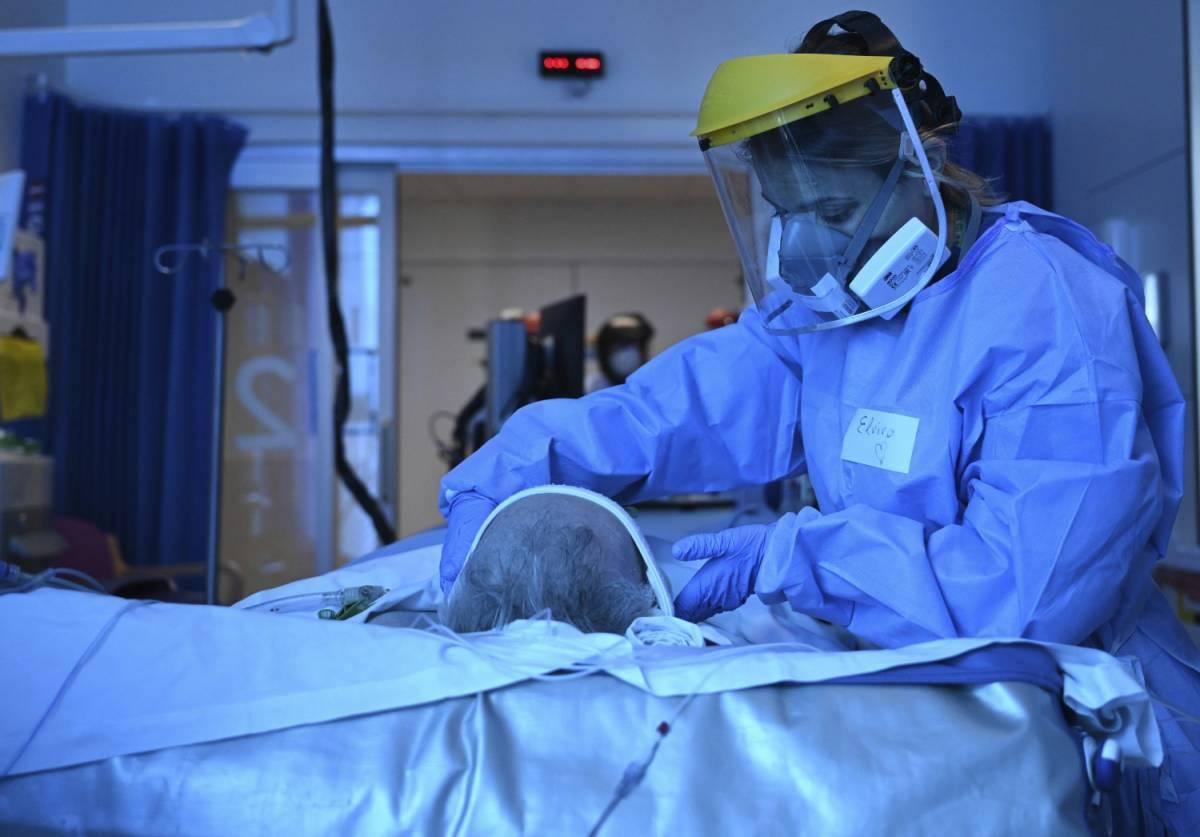 Un medico indossa i dispositivi di sicurezza per trattare il paziente (LaPresse)
