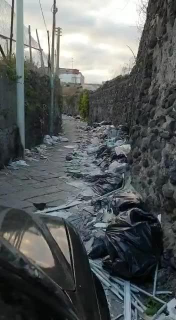 I rifiuti che invadono la carreggiata lungo la strada