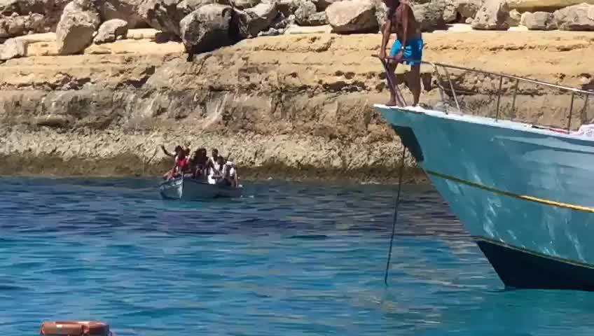 Sbarco di migranti a Lampedusa tra le barche dei turisti