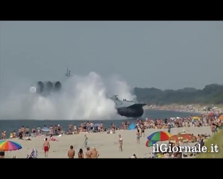 Nave militare attracca sulla spiaggia affollata